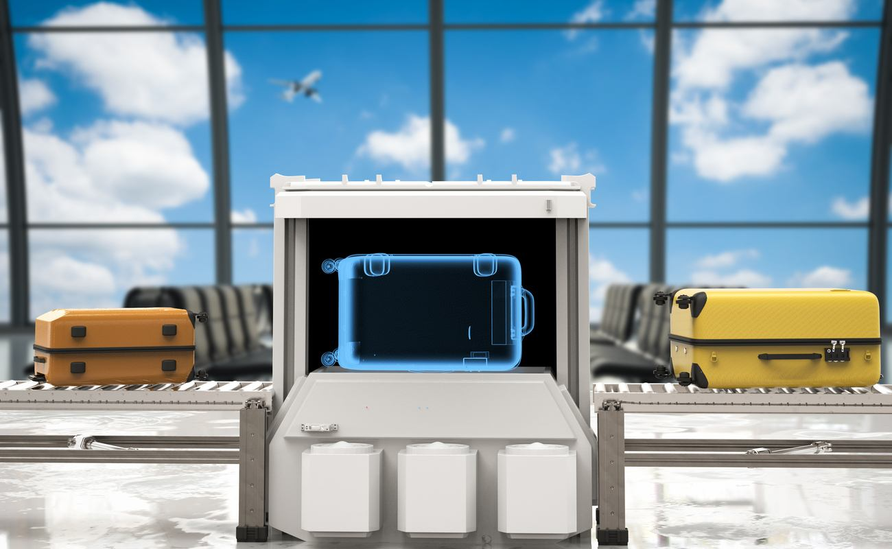 Suitcase on airport security conveyor belt passing through screening with multiple suitcases waiting in line.