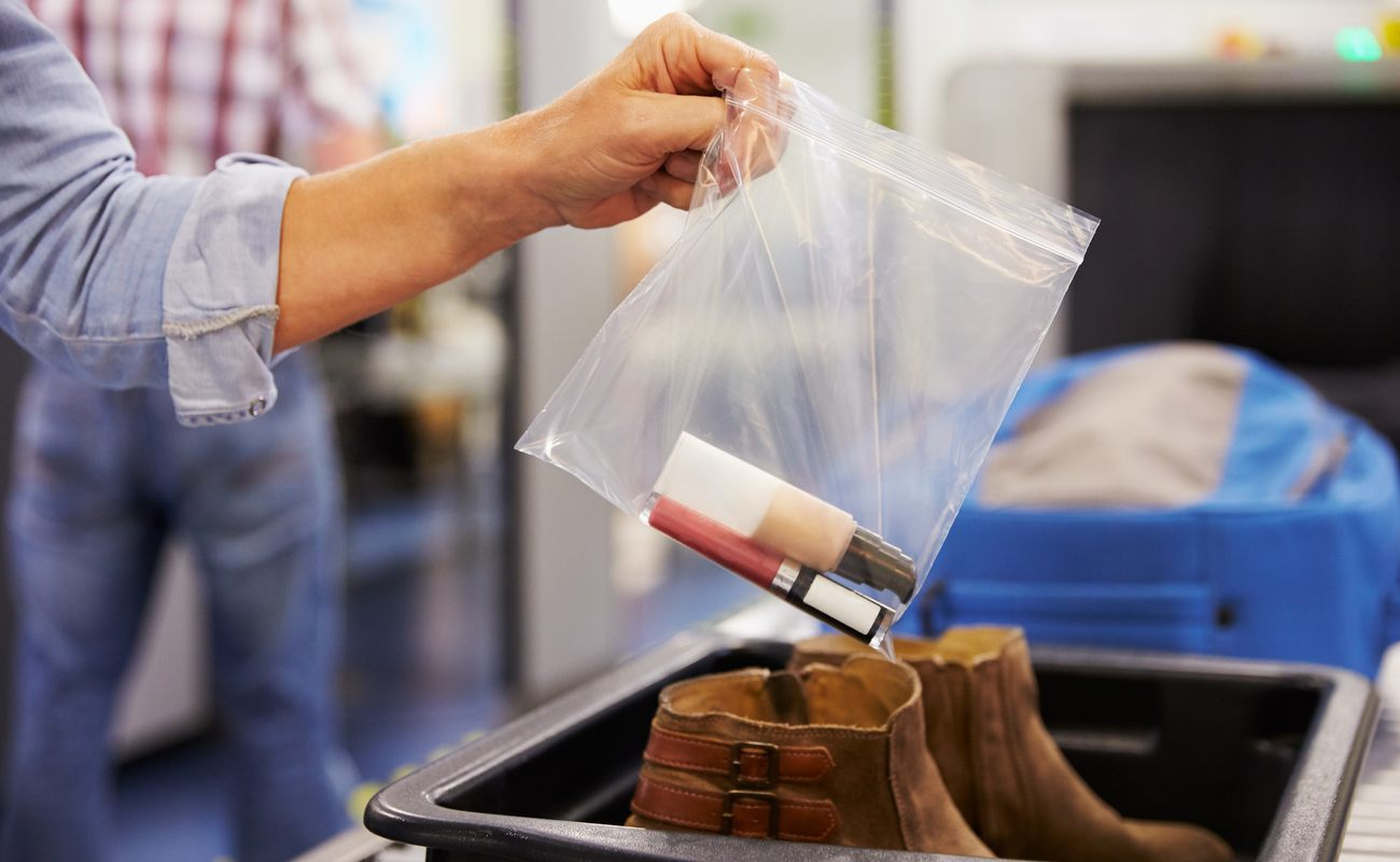 Woman holding a clear zip-lock bag with a lipstick and foundation bottle in placing the bag into an airport security tray.