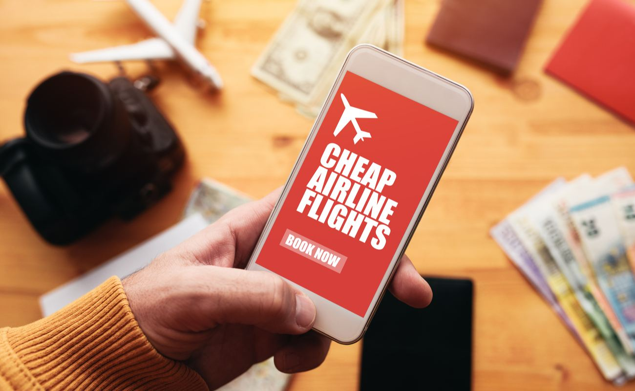 Person using a cheap airline flight app with BOOK NOW in bold writing with a toy airplane, camera and cash blurred in the background.